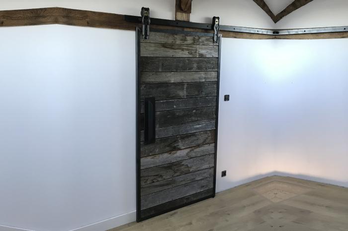 Porte coulissante sur rail métallique châtaignier vieilli pour une porte chambre JPBriand